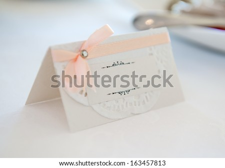White place card decorated with orange bow