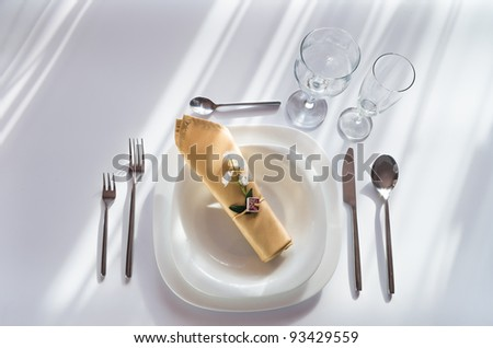 white place setting with plates forks glasses beige napkin and little flower - stock photo