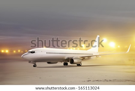 white plane in airport at non-flying weather, blowing snow  - stock photo
