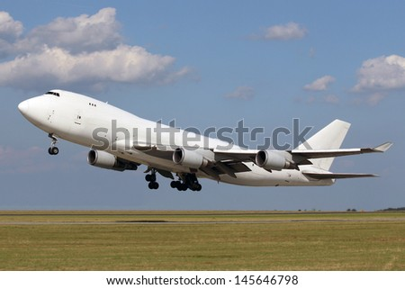 White plane taking off with clouds in the blue sky - stock photo
