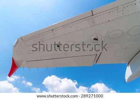 White plane wing on a blue sky background. Travel wallpaper, summer. - stock photo