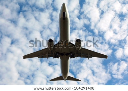 white plane with the gear against the blue sky, view from below - stock photo