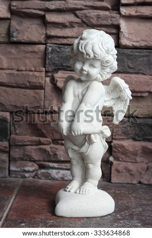 White plaster figurine Angel Cupid on a brick wall a background. - stock photo