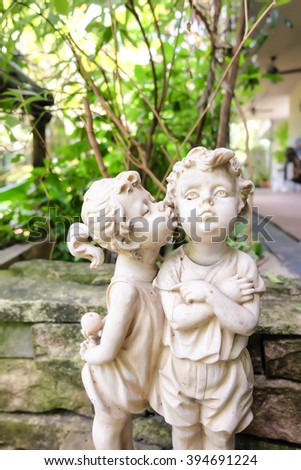 White plaster figurines of girl kissing boy as garden decorations, love and romantic concept, selective focus, blur background  - stock photo