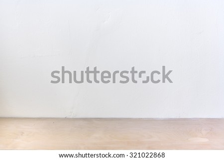 white plaster wall with wooden shelf under it - stock photo