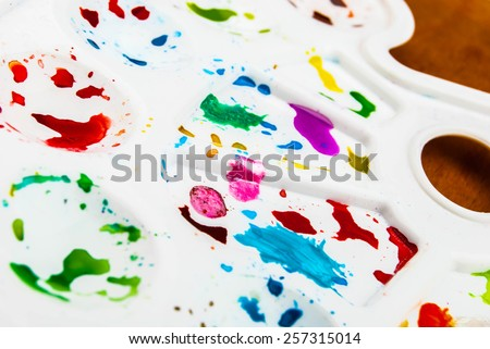 White plastic art palette with random watercolor paint blobs on wood - stock photo