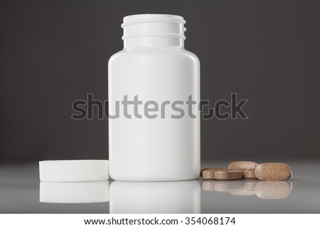 white plastic bottle of supplements and pills beside it - stock photo