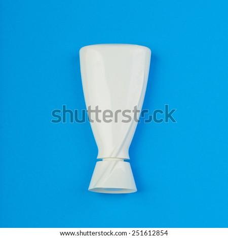 White plastic bottle on a blue background - stock photo