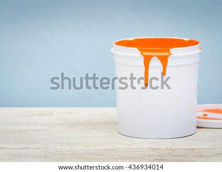 White plastic bucket with orange color paint on wood, vintage background - stock photo