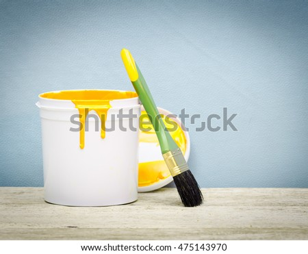 White plastic bucket with yellow color paint and brush on wood,vintage background