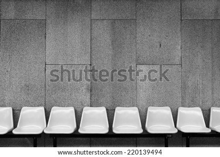 White plastic chairs on cement wall - stock photo