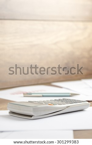 White plastic desk calculator on a printed document, work papers  or assignment, on a wooden desk or workspace, close-up. Suitable for business, accounting, education or science  and research concept.
