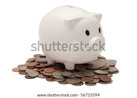 White plastic piggy bank on a pile of us currency coins. Isolated on white background, saved with clipping path
