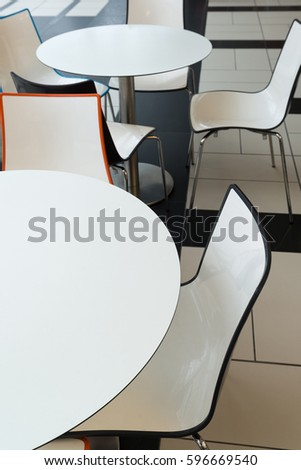 White plastic tables and chairs in a cafe