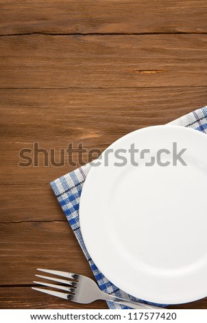 white plate and fork at napkin on wooden background