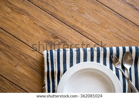 white plate and fork on old wooden table with checked tablecloth and copy space good