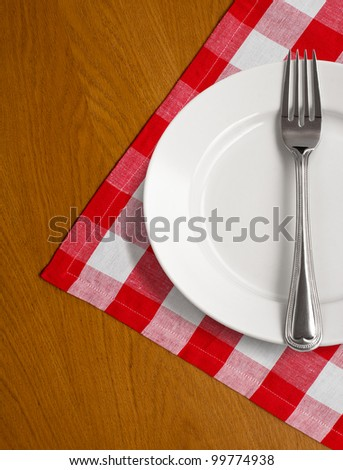 white plate and fork on wooden table with red checked tablecloth - stock photo