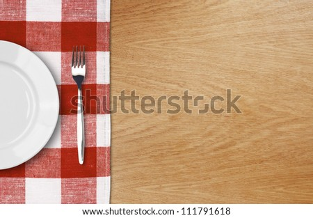 white plate and fork on wooden table with red checked tablecloth and copyspace - stock photo