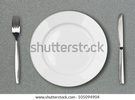 White plate, fork and knife top view on gray plastic textured table surface - stock photo