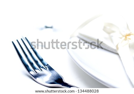White plate, fork and napkin on light background. High key image.