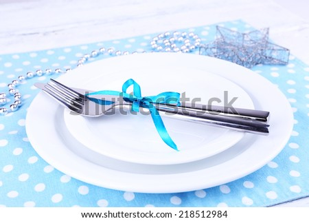 White plate, fork, knife and Christmas decoration on polka dot napkin on wooden background - stock photo