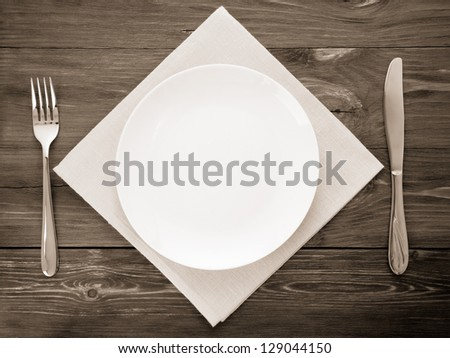 white plate, knife and fork at napkin on wooden background