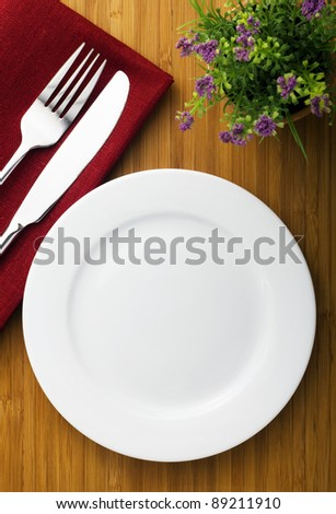 white plate, knife and fork on wood table - stock photo