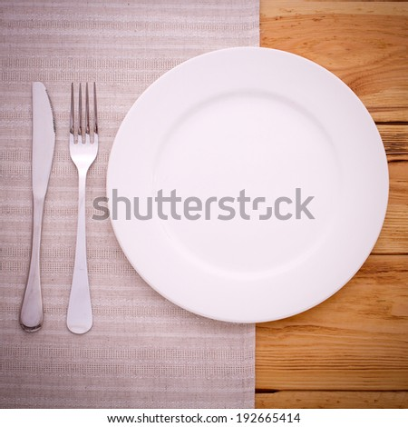White plate, knife and fork on wooden table with tablecloth and copyspace
