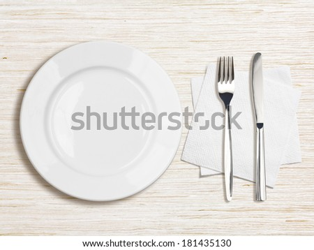 white plate, knife, fork and napkin top view on wooden table - stock photo