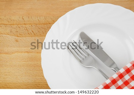 White plate, knife, fork  nd tablecloth on wooden table