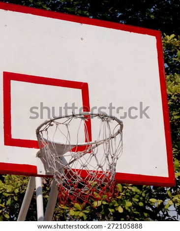 white plate of basketball hoop standing outdoor in a community park with green surrounding for village children to play and have exercise as free sport and healthy infrastructure concept - stock photo