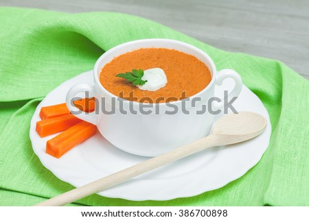 White plate of carrot cream soup. Over old wooden table