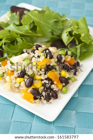 White plate of quinoa and vegetable salad on a blue mat