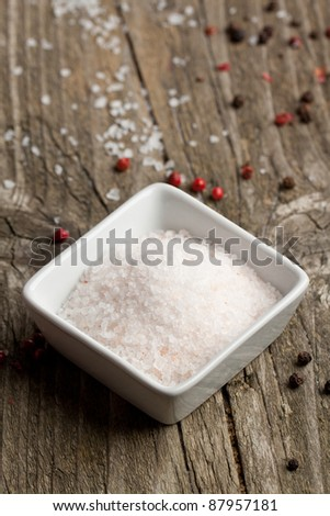 White plate of rose sea salt and pepper on old wooden table - stock photo