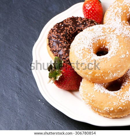 White plate of sugar and chocolate donuts and fresh strawberries served over black stone table. Square image with selective focus - stock photo