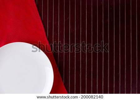 White plate on a red napkin with wooden background. - stock photo