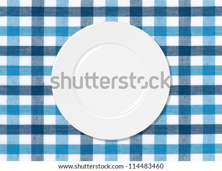 White plate on blue and white tablecloth background - stock photo