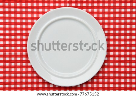 White Plate on red and white checkered background - stock photo