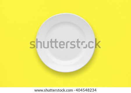 White plate on yellow table top view - stock photo