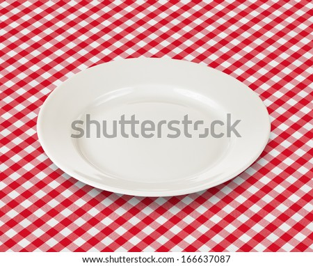 white plate over red checked picnic tablecloth