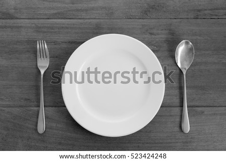 white plate, spoon and fork on wood table, black and white tone