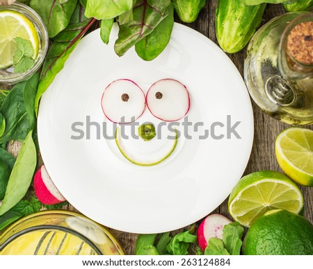 White plate with a smile of spring ingredients surrounded by spring salads and vegetables. Concept of healthy food. selective Focus - stock photo