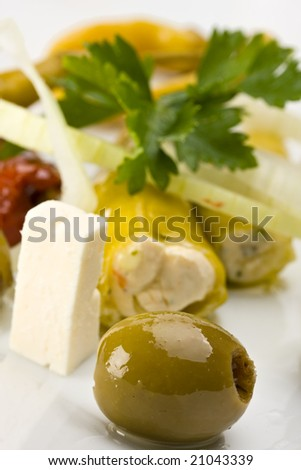 white plate with antipasti - olives, tomatoes and peperoni