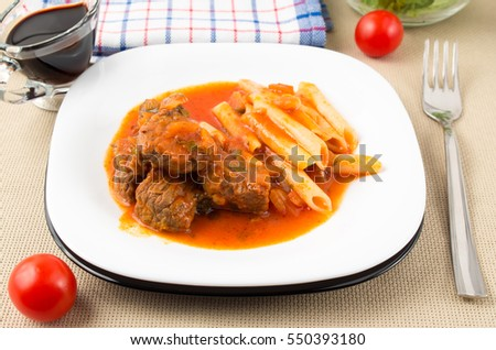 White plate with beef goulash with penne pasta in vegetable sauce on a dining table
