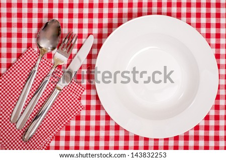 White plate with cutlery of spoon, fork and knife