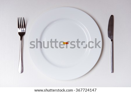 White plate with fork and knife lying on a white background