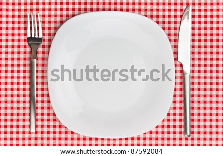 White plate with fork and knife on table.