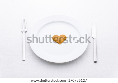 white plate with fork and knife with broken gingerbread heart isolated on white background.