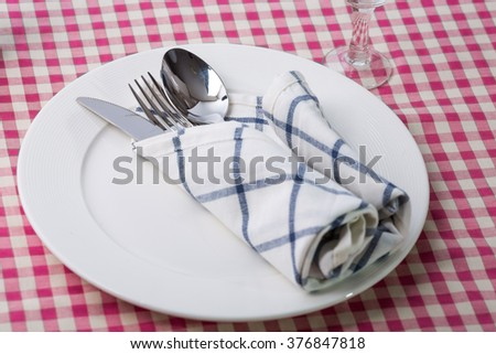 White plate with fork and spoon and knife for dinner - stock photo