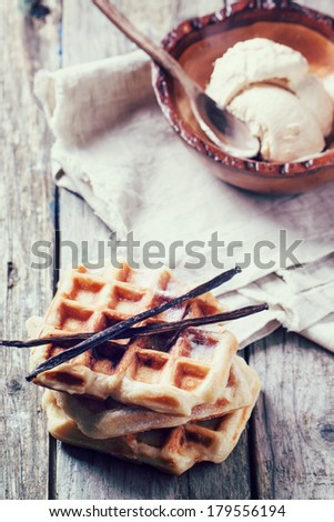 White plate with fresh belgian waffles, served with ice cream and vanilla sticks over wooden table in retro filter effect - stock photo